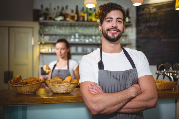 Smiling waiter standing with arms crossed in café