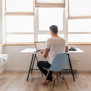 modern young handsome man in casual outfit sitting at table working on laptop, freelancer at home, view from back