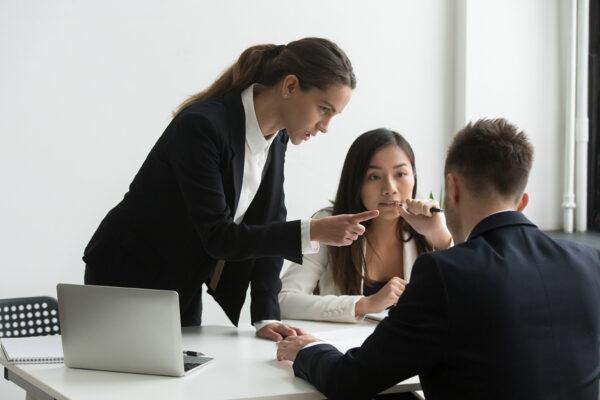 Dissatisfied female executive blaming threatening male employee
