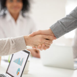 Business partners handshaking at group meeting making project in