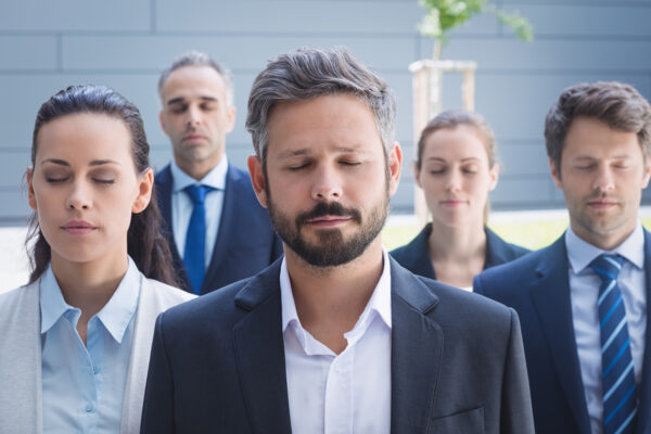 Group of business people with eyes closed standing outside office building