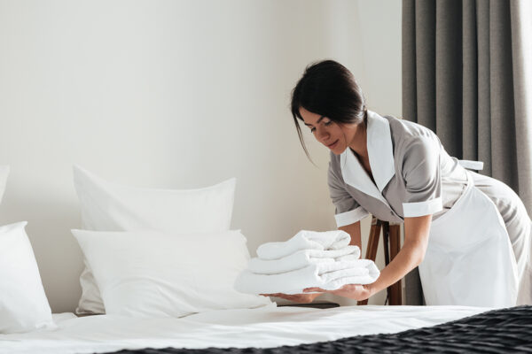 Young hotel maid putting stack of fresh white bath towels