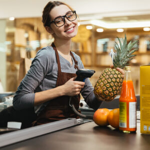 Happy female cashier scanning grocery items